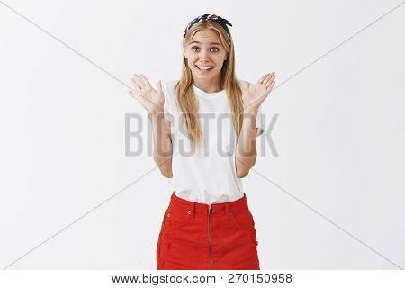 Cute Silly Caucasian Girl With Fair Hair In Stylish Headband And Red Skirt, Raising Palms In Surrend