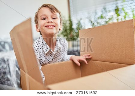 Happy boy moving to house with moving box helps packing