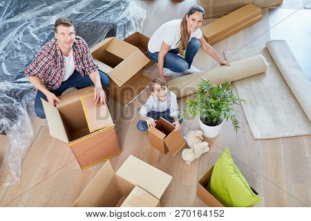 Parents and child moving to a new house as a home with moving boxes