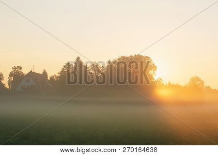 Beautiful Foggy Sunrise Landscape. Scenic Mist Over The Meadow And A Rural House In The Woods.