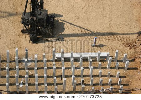 Field Piles At The Construction Site And A Pile Driver