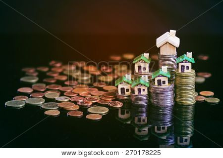 Image For Property Investment. Creatively Lit Green House And Stacked Coins Against A Black Backgrou