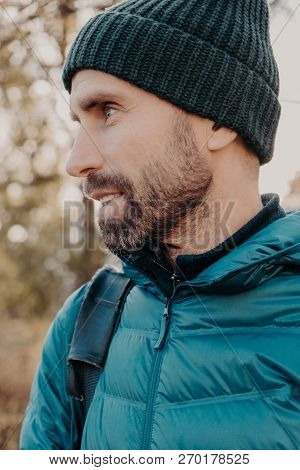Sideways Shot Of Unshaven Man With Dark Thick Beard, Wears Warm Har And Anorak, Looks Pensively Asid