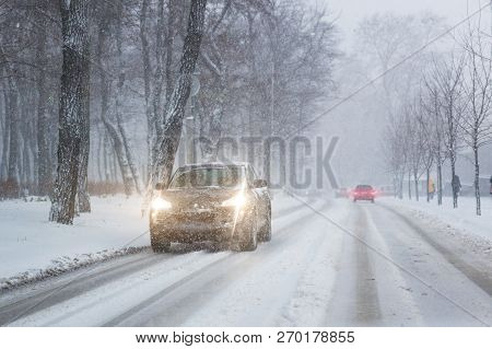 Cars Moving On Slippery Snowy Road At City Street During Heavy Snowfall At Evening In Winter . Traff