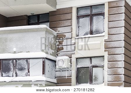 Wall With Windows Of Modern High-rise Apartment Building Covered With Snow And Frost After Heavy Win