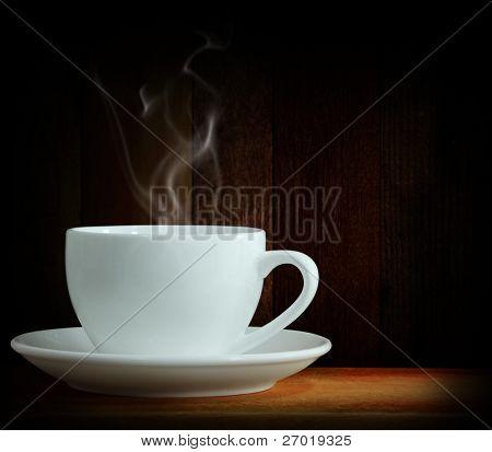 Café negro caliente sobre la madera de la mesa