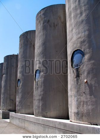 Four Greyish Wine Containers In Line Against A Blue Sky.