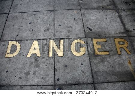 Metal Words in the Sidewalk. Old Metal Words imbedded in cement. The word DANGER written in Brass Letters Cemented into the sidewalk.