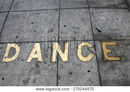 Metal Words in the Sidewalk. Old Metal Words imbedded in cement. The word DANCE written in Brass Metal cemented into a sidewalk outside.