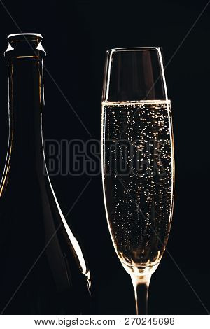 Half Of Glass And Half Of Bottle Of Champagne Isolated On Black Background. Macro, Vertical. Alcohol