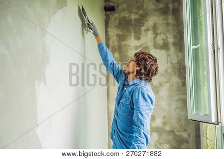 master is applying white putty on a wall and smearing by putty knife in a room of renovating house in daytime poster