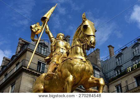 Paris, France. Joan of Arc (Jeanne d'Arc) golden statue. Blue sky with white clouds.