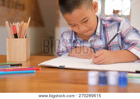 Little Asian Kid Boy Child Schoolboy Drawing Picture. Children Leisure Activity At Home