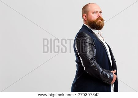 Man with beard stands sideways