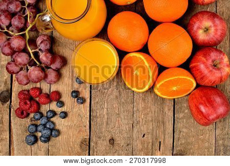 View From Above Of Jug With Orange Juice, Fresh Oranges, Apples, Grapes, Raspberries And Blueberries