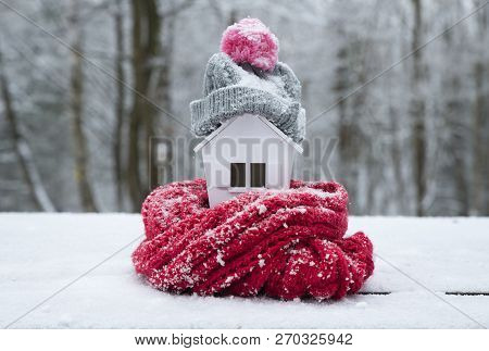 House In Winter - Heating System Concept And Cold Snowy Weather With Model Of A House Wearing A Knit
