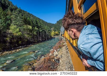 Young Man Looking Out Of Train Window On The Historic Steam Engine Train Travelling From Durango To