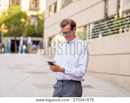Smiling Attractive Stylish Mature Man Using Smart Phone In Urban Outdoors City