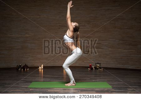 Slim Young Lady Practicing The Chair Pose While Being Alone