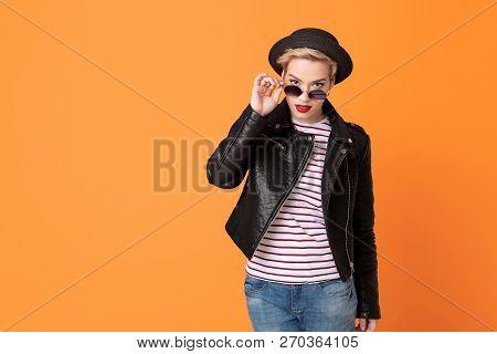 Stiylish Blonde Girl Wearing Leather Jaket And Hat Look Over Glasses On Orange Background, Copy Spac