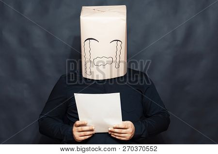 The Concept Of Emotions. A Man Is Reading A Letter. On The Face, An Expression Of Resentment And Pit