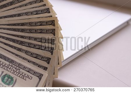 Dark Photo Of A Fan Of 100 Dollar Bills On A Blurred Background. Selective Focus. Unfolded Stack Of