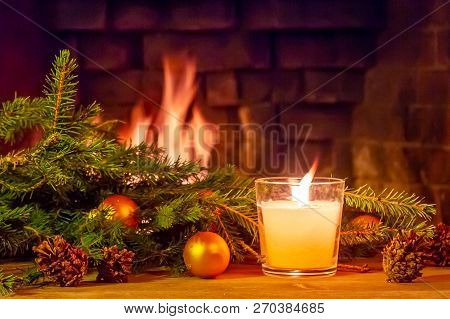 Branches Of A Christmas Tree, Decorations, A Candle On A Wooden Table In Front Of The Fireplace. New