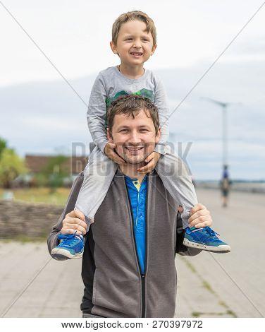 Happy Father Giving Shoulder Ride On His Shoulders In Garden. Happy Smiling Boy On Shoulder Dad Look