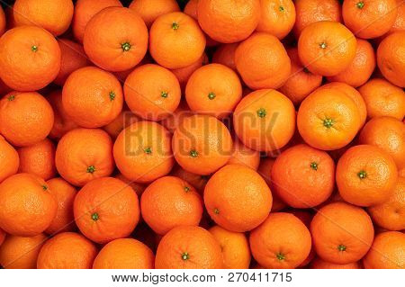 Profusion Of Fresh Mandarin Oranges Fruits Or Tangerines With Leaves As Background