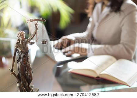 Lawyer Office. Statue Of Justice With Scales And Lawyer Working On A Laptop.