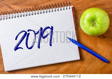 2019 Written On A Notepad With An Apple