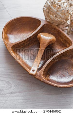 Still Life Of A Wooden Salad Bowl Of Three Sections, A Wooden Spoon And Wooden Decor On A Wooden Bac