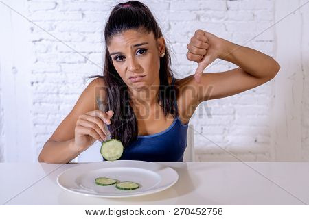 Depressed Dieting Woman Holding Folk Looking At Small Green Vegetable On Empty Plate