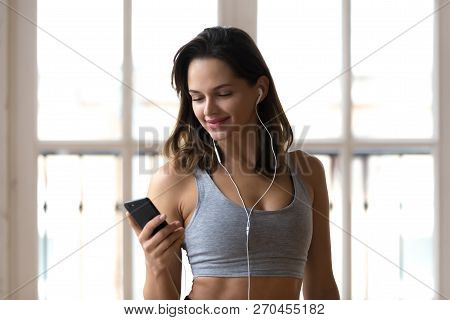 Positive Sporty Girl Using Smartphone Listening Music During Wor