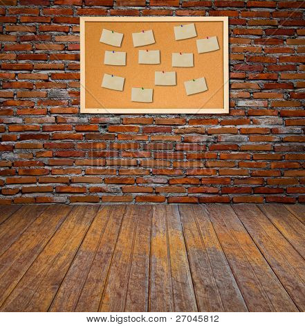Cork bulletin board with old paper note on brick wall.