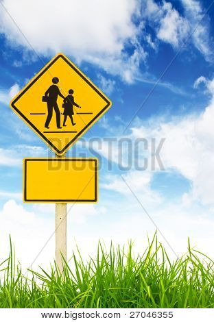Traffic sign (School warning sign) on green grass and blue sky.
