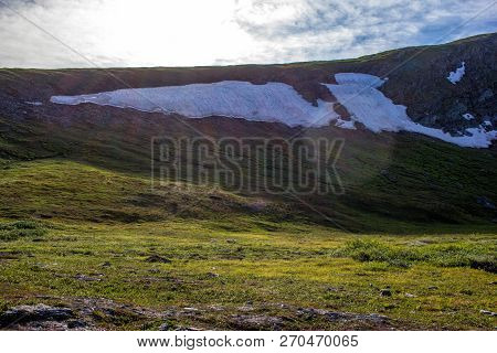 A Large Snowfield On The Mountainside. Nature Of The Northern Urals. Never Melting Snow In The Mount