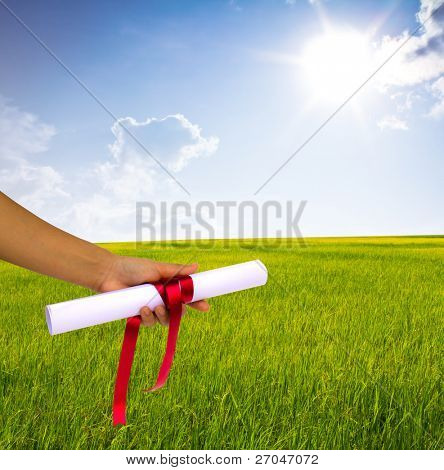Hand holding Diploma wrapped with a red ribbon.