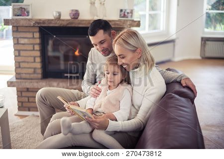 Beautiful Family Sitting By The Fireplace. Mom, Dad And Girl Are Reading A Book. Motherhood. Family.