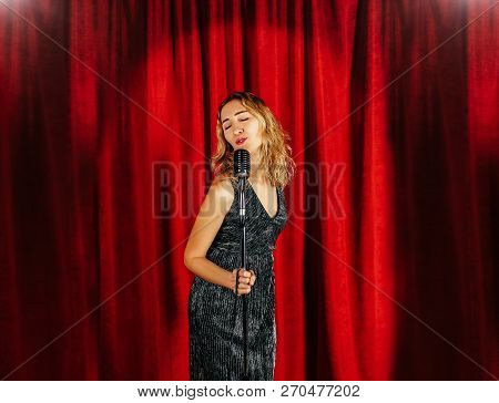 Young Attractive Girl Singing On Stage With Microphone Against The Background Of Red Curtains