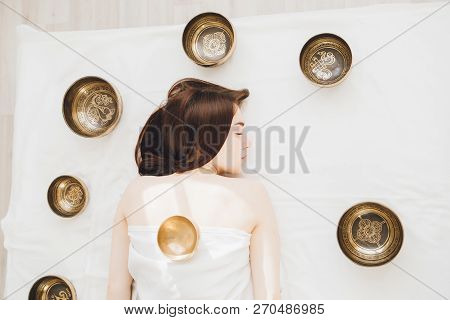 Girl Doing Massage Therapy Singing Bowls In The Spa