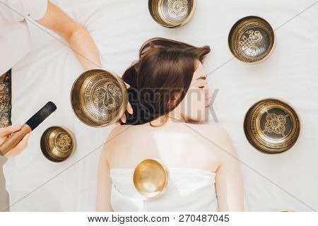 Young Beautiful Girl Doing Massage Therapy Singing Bowls In The Spa. The Concept Of Relaxation And A