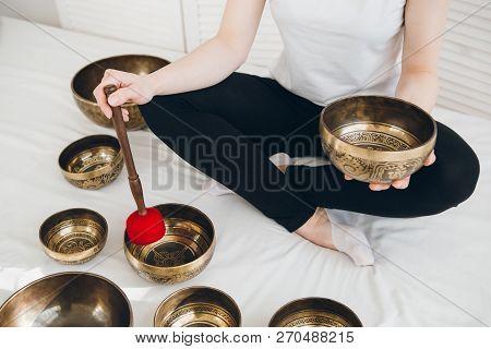 Massage Therapist Plays On Singing Bowls For A Vibrational Massa