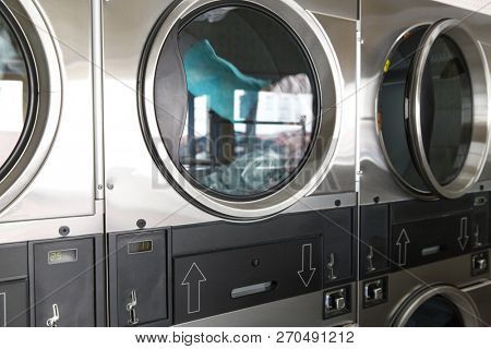self-service laundry facilities concept - washing machines with clothes inside at laundromat poster