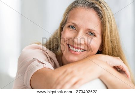 Portrait of happy senior woman relaxing on sofa. Closeup face of mature blonde woman smiling and looking at camera. Retired lady in casual leaning on couch.