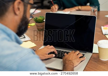 Back view of businessman sitting in front of laptop screen. Businessman typing on laptop in office.  Multiethnic casual man typing on empty screen computer sitting at wooden table.