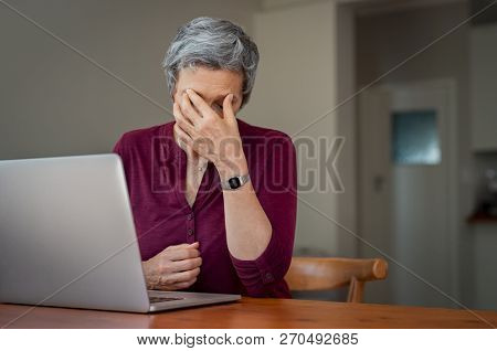 Mature businesswoman suffering a stress headache sitting at her desk with closed eyes in pain. Depressed tired senior lady suffering from chronic daily headache from computer.