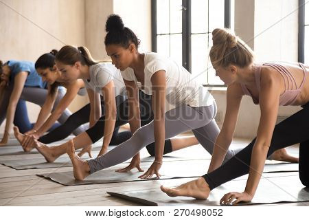 Group Of Women Practicing Yoga Lesson, Doing Half Splits Exercis