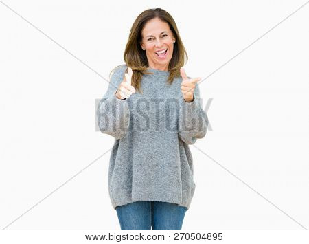 Beautiful middle age woman wearing winter sweater over isolated background approving doing positive gesture with hand, thumbs up smiling and happy for success. Looking at the camera, winner gesture.