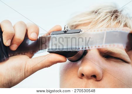 Male Uses The Old Vintage 35mm Film Negative Viewer To See A Frames On The Vintage Camera Slides